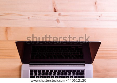 Laptop layid on wooden office desk. Studio shot. - stock photo