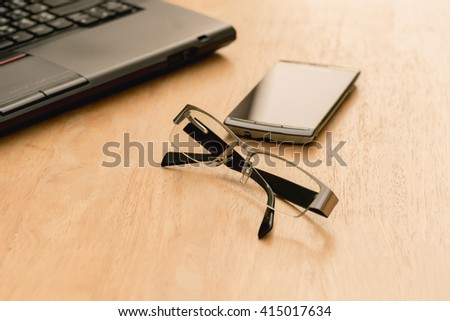 Laptop, mobile phone and glasses on wood table - stock photo