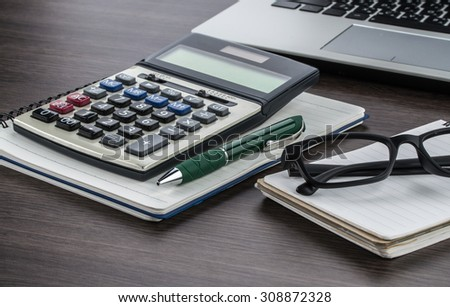 laptop, notebook and pen with calculator on the desk finance plan - stock photo