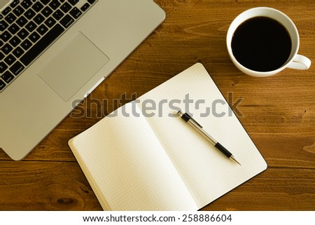 Laptop, notepad and coffee cup on wood table. View from above. - stock photo