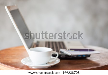 Laptop, notepad and coffee cup on wooden table