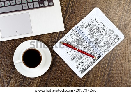Laptop notepad with sketches and cup of coffe on table - stock photo