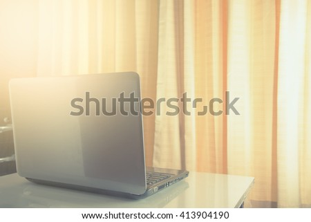 Laptop on a desk/vintage style and effect sun lighting - stock photo