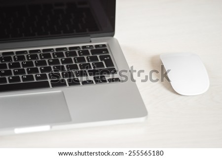 Laptop on a light table with a mouse - stock photo