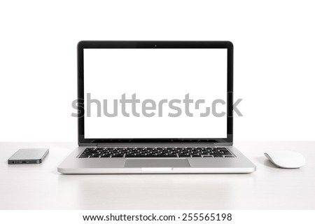 Laptop on a light table with a mouse and a telephone - stock photo