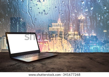 Laptop on building high angle background city on rainy days. - stock photo