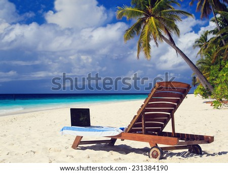 laptop on chair in tropical beach vacation