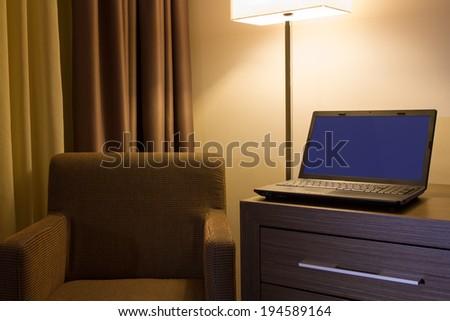 Laptop on desk in hotel room - stock photo