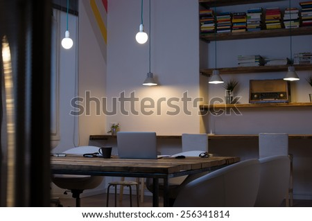 Laptop on desk with empty chairs in modern office