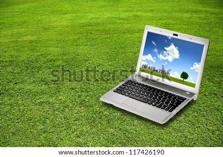 Laptop on green grass. A concept of green technology. You can change the laptop screen to suit your design purpose - stock photo