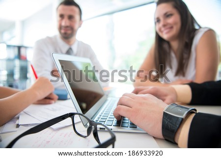Laptop on office table with male hands working - stock photo