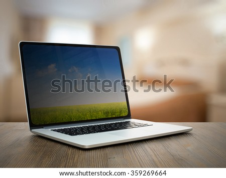laptop on old wooden table in the bedroom - stock photo