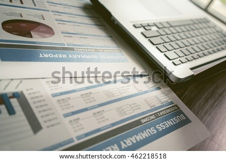 Laptop on table with business report on table