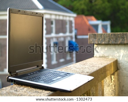 Laptop on the edge of a balcony