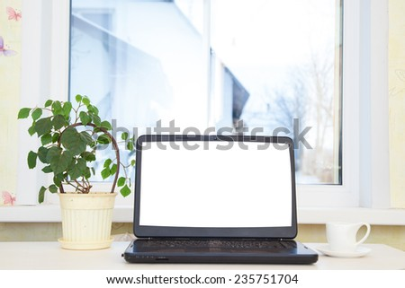 Laptop on the table against the window - stock photo
