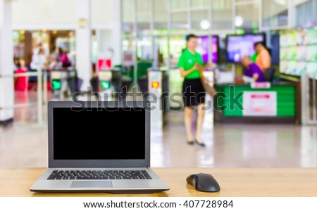 Laptop on the table,blur image of check point in building as background. - stock photo