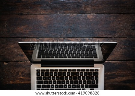 Laptop on the wooden background from above,selective focus  - stock photo