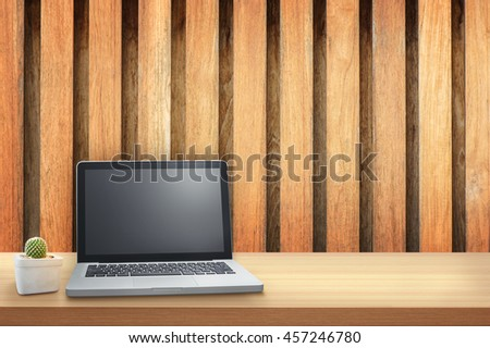 laptop on wood table with wood wall