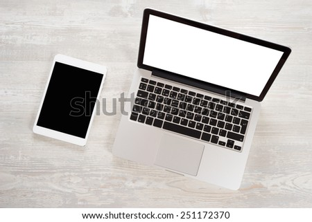 Laptop on wooden table notebook and tablet - stock photo