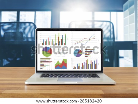 Laptop on wooden table showing charts and graph against office background ,Analysis Business Accounting, Statistics Concept. - stock photo