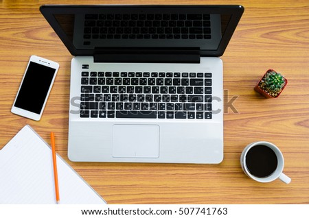 laptop on wooden table with coffee cup, phone, book and cactus on top view