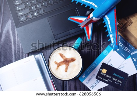 Laptop, plane tickets, coffee, cappuccino and credit card lies on the table. The view from the top. The concept of travel and transport