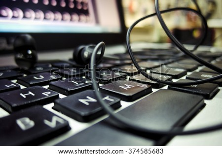Laptop power button on the headphones on the screen are the keys wire blurred background