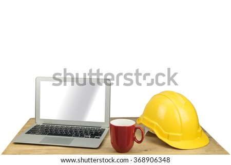 laptop, red mug and safety helmet on wood table with white background - stock photo