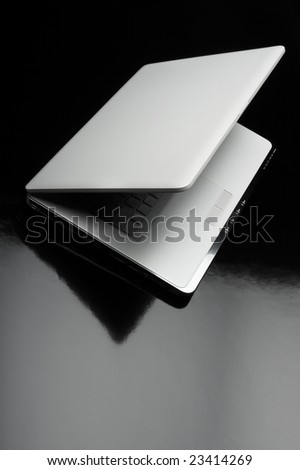 Laptop shot on reflective table - stock photo