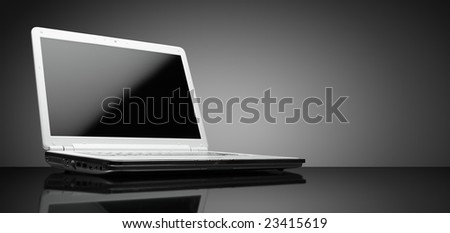 Laptop shot on reflective table on grey background, clipping path for display - stock photo