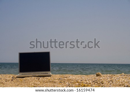 Laptop sitting on sand with sea and blue sky behind - stock photo