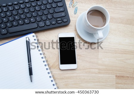 laptop, smartphone and cup of coffee on wooden table, view from above, soft focus