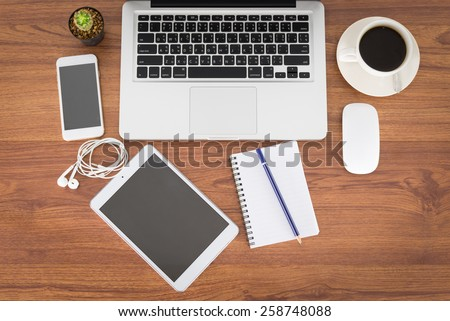 Laptop, smartphone,tablet and coffee cup with financial documents on wooden table - stock photo