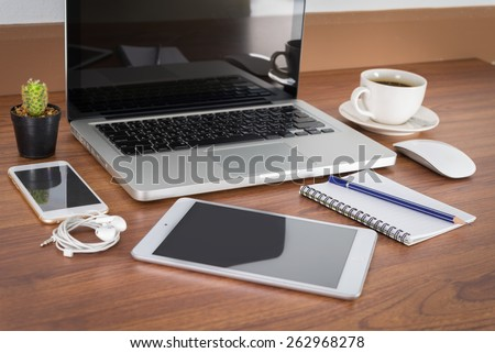 Laptop, smartphone, tablet and coffee cup with financial documents on wooden table - stock photo