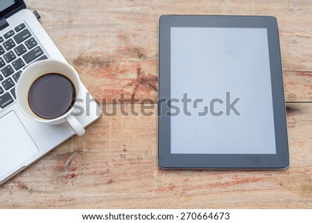 Laptop, smartphone, tablet and coffee cup with financial documents on wooden table