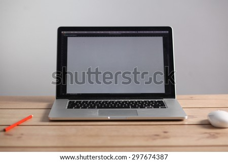Laptop stands on a wooden table
