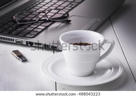Laptop stick, glasses and a cup of coffee on a white wooden table