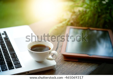 Laptop, tablet, smartphone and a white cup of coffee on wooden background.