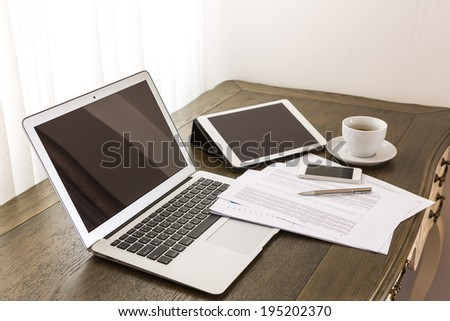Laptop, tablet , smartphone and coffee cup with financial documents on wooden table - stock photo