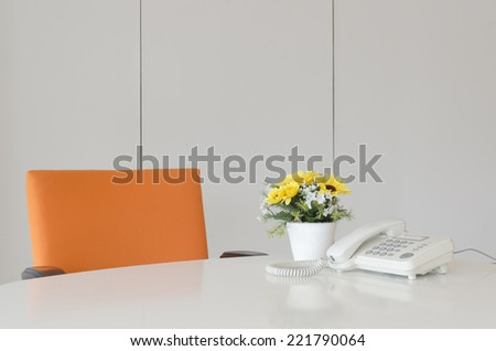laptop telephone and flower in vase on desk, work space - stock photo