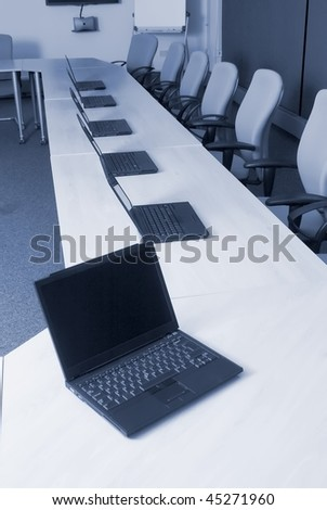 Laptop, white board, video conference equipment in college training room - stock photo
