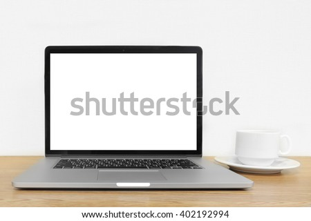 laptop with a cup of coffee on the office wooden table
