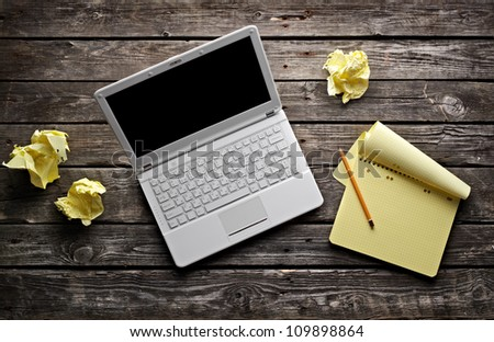 Laptop with blank notepad and pencil with sheets of crumpled paper on old wooden table. Workplace writer or designer. - stock photo
