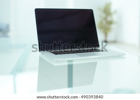 Laptop with blank screen on table in office