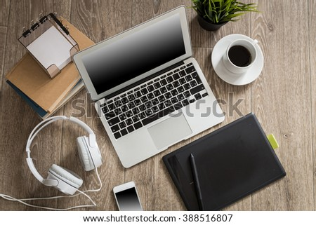 Laptop with blank screen on table in office room