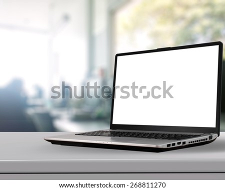 Laptop with blank screen on white desk with blurred background as concept - stock photo