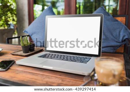 Laptop with blank screen on wood table. gray color laptop white screen and smartphone and coffee cup in cafe vivid tone.   - stock photo