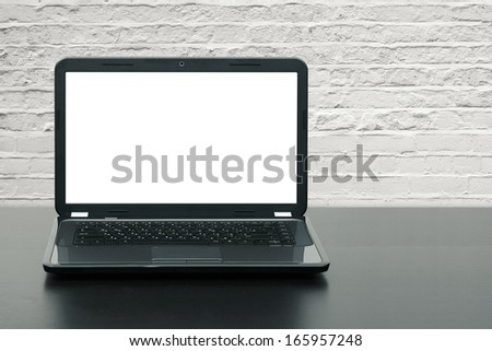 laptop with blank screen on wooden table at brick wall - stock photo