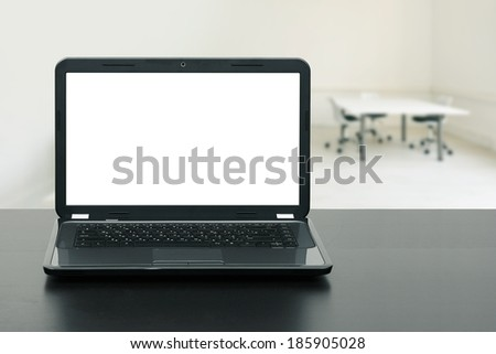 laptop with blank screen on wooden table in the office - stock photo