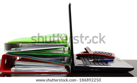 Laptop with calculator and company documentation on desk - stock photo